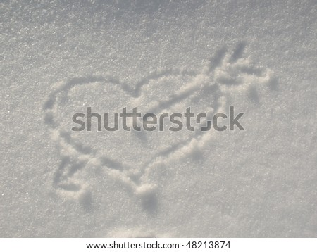 Heart pierced by an arrow painted on the snow - stock photo
