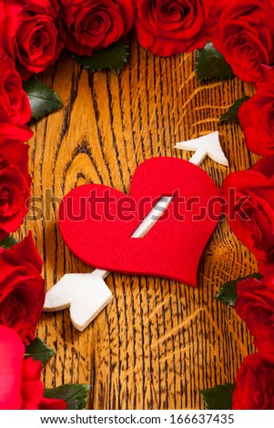 heart pierced by  cupid arrow and red roses on the wooden background - stock photo