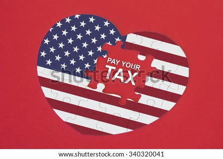Heart shape America Flag jigsaw puzzle with a written word Pay Your Tax with red background - stock photo