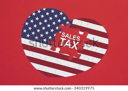 Heart shape America Flag jigsaw puzzle with a written word Sales Tax with red background - stock photo