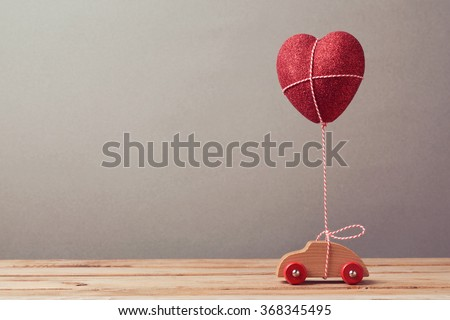 Heart shape balloon and car toy on wooden table. Valentine's day concept. - stock photo