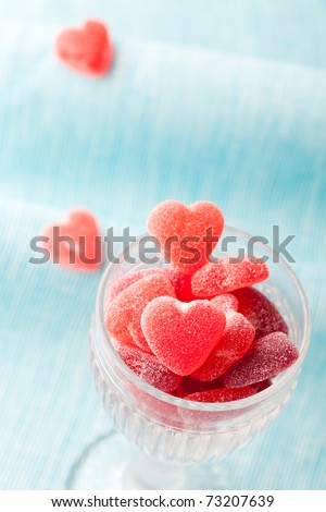 Heart shape candy in a glass for Valentine's day on a light blue background - stock photo