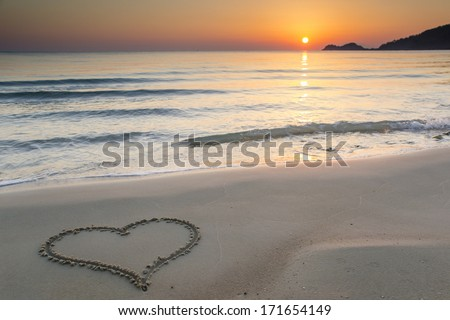 Heart shape drawn on a  sandy beach at sunrise on the beautiful island of Thassos, Greece. - stock photo