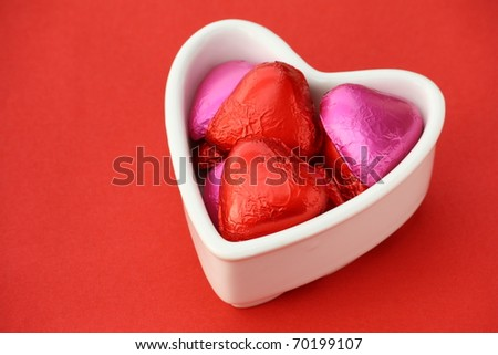 Heart shape foil wrapped chocolates in a white heart shape bowl on a red textured paper background - stock photo