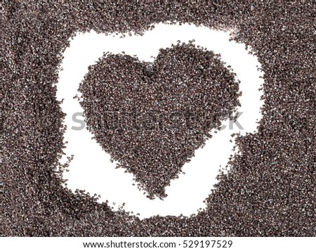 Heart shape formed by poppy seeds over white background