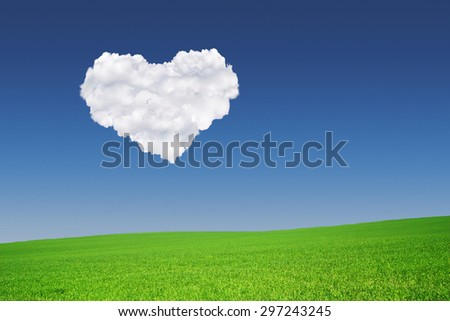 Heart shape formed from clouds in the blue sky above a green meadow - stock photo