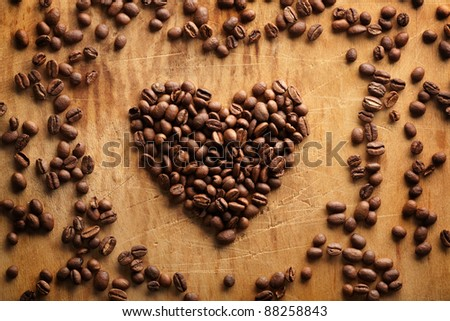Heart shape from brown coffee beans, close-up on old vintage wooden background. - stock photo
