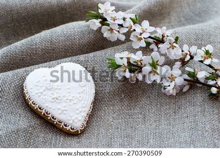 Heart shape gingerbread cookie with icing on sacking - stock photo