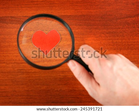 Heart Shape in the Loupe on the Wooden Background - stock photo