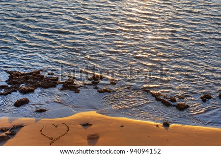 heart shape in the sand on a beach of the mediterranean sea - stock photo