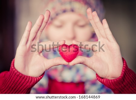 Heart shape love symbol in woman hands with face on background Valentines Day romantic greeting people relationship concept winter holiday - stock photo