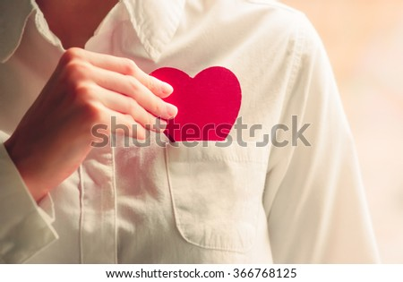 Heart shape love symbol in woman hands with white shirt pocket Valentines Day romantic greeting people relationship lifestyle feelings concept winter holiday  - stock photo