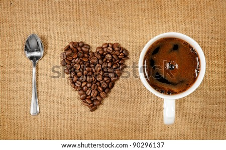 Heart shape made from coffee beans with a spoon and cup of coffee on hessian spelling I love coffee - stock photo