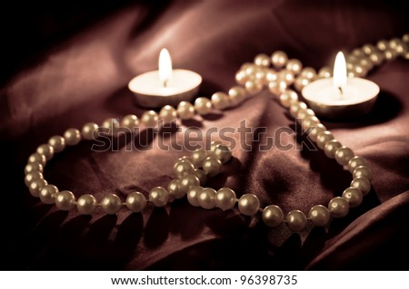 Heart shape made from pearls and two burning candles on the satin - stock photo