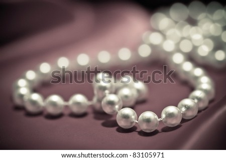 Heart shape made from pearls on the red satin - stock photo