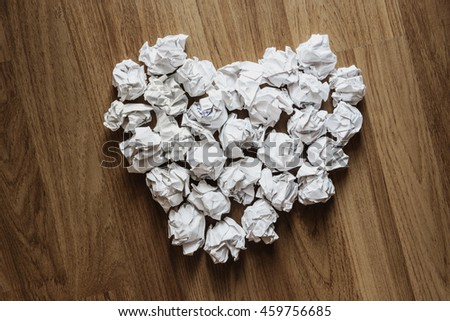 Heart shape made of crumpled paper, on wooden background - stock photo