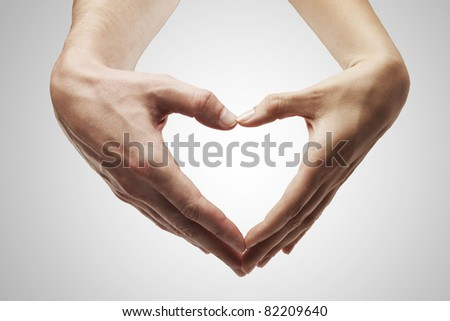 Heart shape  made of  female and male hands together.Isolated on a gray background - stock photo