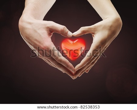 Heart shape  made of  female and male hands together.With a red heart inside. - stock photo