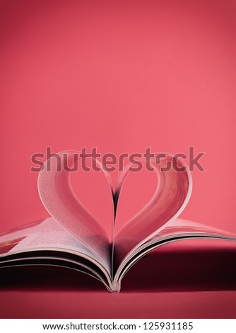 heart shape made of magazine pages on pink background with copyspace - stock photo