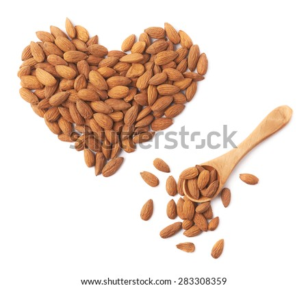 Heart shape made of multiple almond seeds next to the wooden measuring spoon isolated over the white background - stock photo