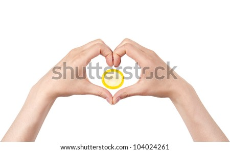 heart shape made of two beautiful palms with condom on white background - stock photo