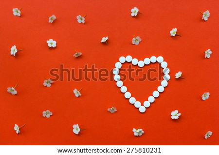 Heart shape made of white pills with white flowers pattern on orange background.Useful as background for medicine, pharmacy, prescription, homeopathy - stock photo