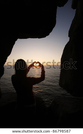 heart shape made with a girl hands at sunset - stock photo