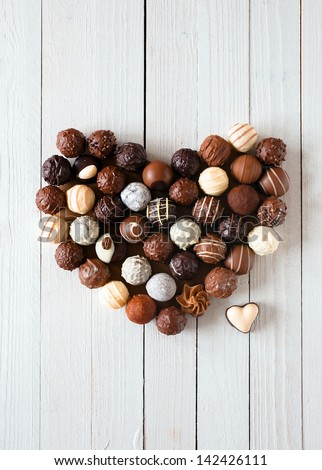 Heart shape made with various types of chocolate truffles over a white wooden table - stock photo