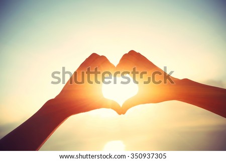 Heart shape making of hands against bright sea sunrise and sunny golden way at water - stock photo