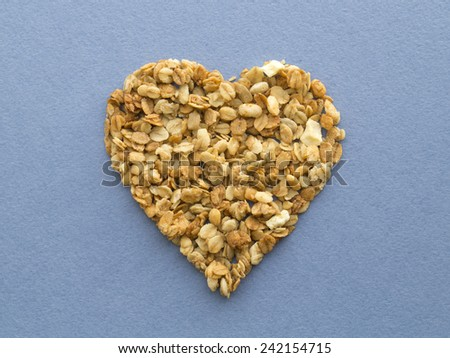 Heart shape muesli on a blue rugged paper background - stock photo