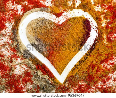 Heart Shape of Colorful Spice Powder Mix Surface - stock photo