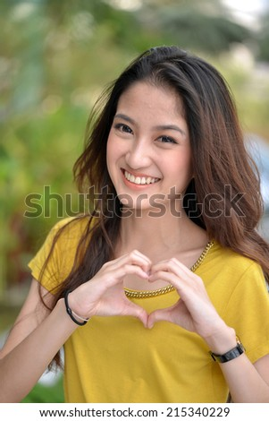 Heart shape of love and smile from Young beautiful woman  - stock photo