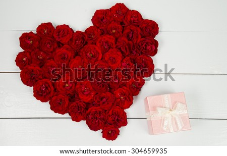 Heart shape of roses on a white table - stock photo