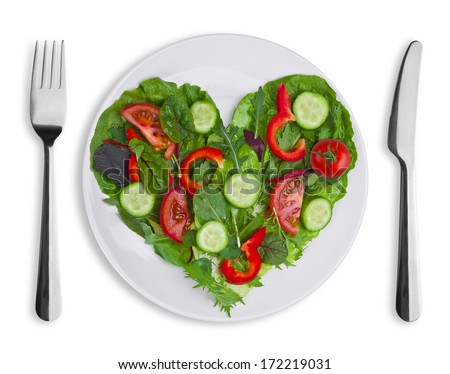 Heart shape of various vegetables and herbs on white plate - stock photo