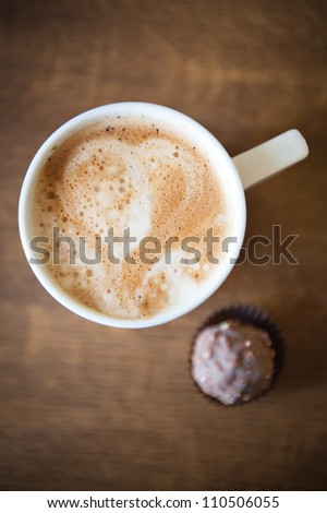 Heart shape on latte over wooden table - stock photo