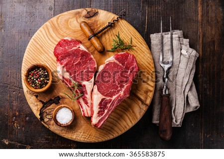 Heart shape Raw fresh meat Ribeye Steak on bone with rosemary, pepper and salt on dark wooden background - stock photo