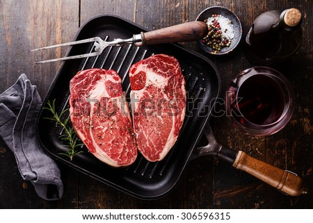 Heart shape Raw fresh meat Steak Ribeye with rosemary and pepper on grill pan on wooden background - stock photo