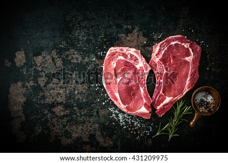 Heart shape raw fresh veal meat steaks with rosemary, pepper and salt on dark background - stock photo