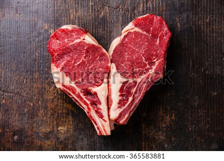 Heart shape Raw meat Ribeye steak entrecote on bone on wooden background - stock photo