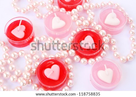 Heart shape red and pink candles with necklace  isolated on grey background.