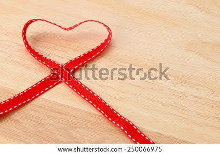 Heart shape red ribbon placed on the wooden floor. - stock photo