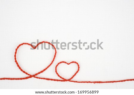 Heart shape rope on white fabric - stock photo