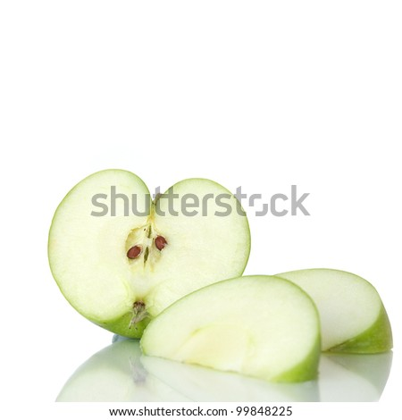 Heart-shape sliced green apple with cut segments on a reflective surface against a white background. Copy space. - stock photo