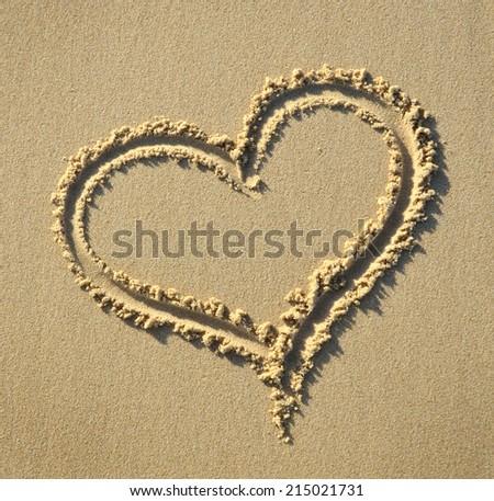 Heart shape symbol drawn on sandy beach - stock photo
