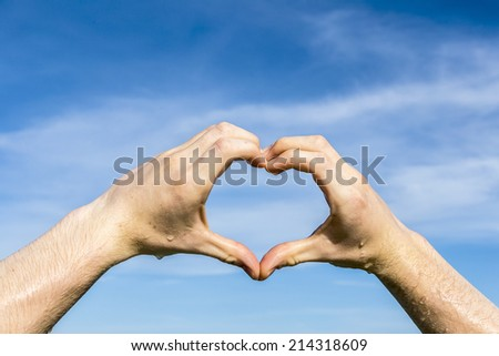 heart shape with hand under blue sky in sun