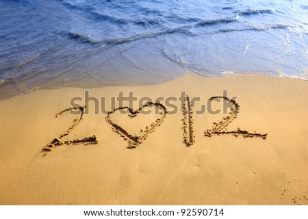heart shape with happy new year 2012 on the beach of sunrise - stock photo