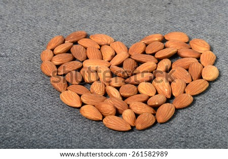 Heart shaped Almonds on sackcloth background  - stock photo