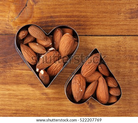 Heart shaped almonds on wooden table, copy space. Healthy eating. Good fats, Prevention for high cholesterol and blood pressure