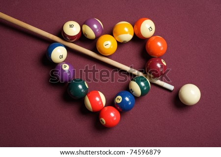 heart-shaped billiard balls with cue ball and stick - stock photo