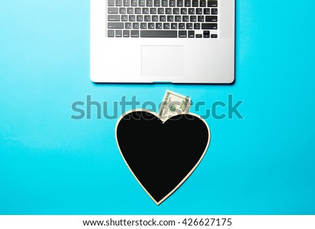 heart shaped board, money and laptop on the blue background - stock photo